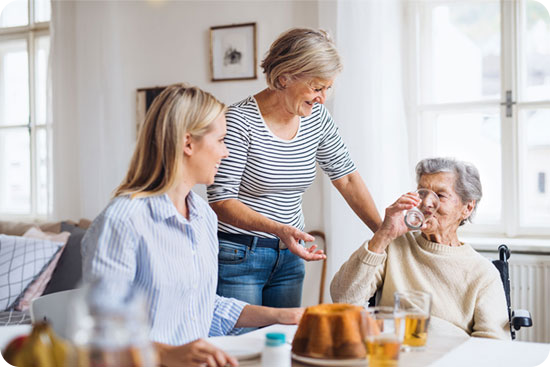 Ältere Dame wird von zwei Assistentinnen versorgt