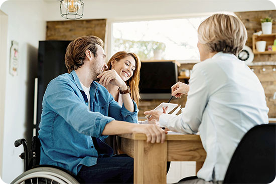 Junges Paar sitzt mit Pflegeberaterin am Tisch und ist offensichtlich gut gelaunt.